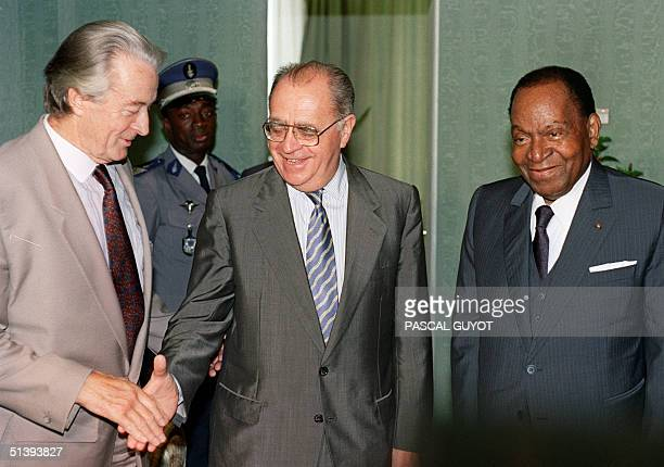 French Premier Pierre Beregovoy shakes hands with his Foreign Minister Roland Dumas during the 17th FranceAfrica summit 06 October 1992 in Libreville...
