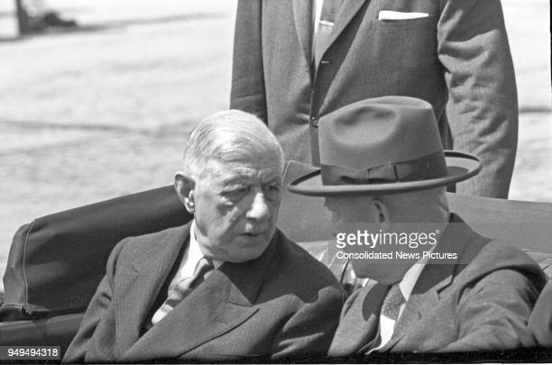 French President Charles de Gaulle and US President Dwight D Eisenhower talk together as they ride in a limousine as they leave Washington National...