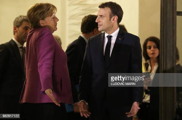 French President Emmanuel Macron accompanies German Chancellor Angela Merkel as she leaves at the Elysee Palace in Paris on March 16 2018 Days after...