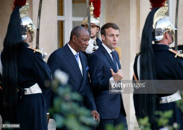 French President Emmanuel Macron accompanies out Guinea's President and President of the African Union Alpha Conde after their meeting at the Elysee...