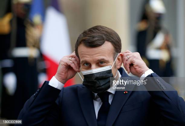 French President Emmanuel Macron adjusts his protective face mask as he welcomes Moldovan President Maia Sandu prior to a working lunch during an...