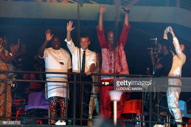 French President Emmanuel Macron and artist Femi Kuti wave to the crowd during a visit to the Afrika Shrine during a live show in Lagos on July 3...