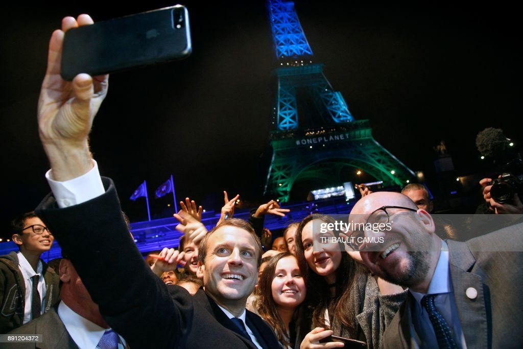 French President Emmanuel Macron (L) and Belgian Prime Minister Charles Michel (R) take a selfie with youths in front of the Eiffel Tower illuminated in green, aboard a boat cruising on the river Seine, after the One Planet Summit in Paris on December 12, 2017. ?The French President hosts 50 world leaders for the 'One Planet Summit', hoping to jump-start the transition to a greener economy two years after the historic Paris agreement to limit climate change. / AFP PHOTO / POOL / Thibault Camus