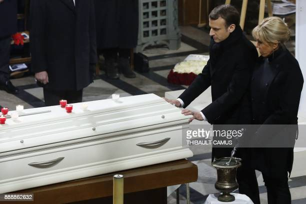 French President Emmanuel Macron and Brigitte Macron stand next to the coffin during the funeral ceremony for late French singer Johnny Hallyday at...