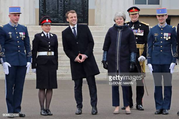 French President Emmanuel Macron and Britain's Prime Minister Theresa May pose for a photograph with French and British military cadets at the Royal...