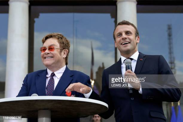 French President Emmanuel Macron and British singer-songwriter Elton John speak to a crowd in the courtyard of the Elysee Palace in Paris, on June 21...