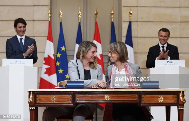 French President Emmanuel Macron and Canadian Prime Minister Justin Trudeau applaud as French Culture Minister Francoise Nyssen and Canadian Heritage...