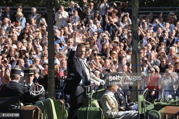 French President Emmanuel Macron and Chief of the Defence Staff French Army General Pierre de Villiers ride aboard a command car during the annual...