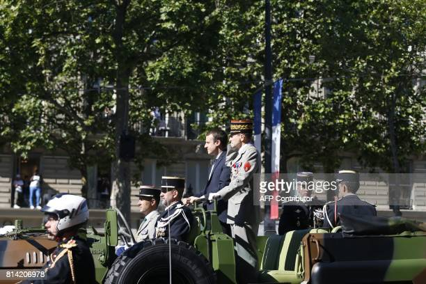 French President Emmanuel Macron and Chief of the Defence Staff of the French Army General Pierre de Villiers arrive in a command car for the annual...