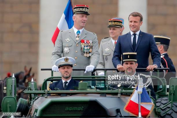 French President Emmanuel Macron and Chief of the Defence Staff General Francois Lecointre stand in the command car as they review troops prior to...