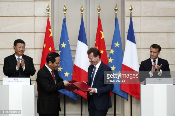 French President Emmanuel Macron and Chinese President Xi Jinping applaud as President of Airbus's commercial aircraft business Guillaume Faury and...