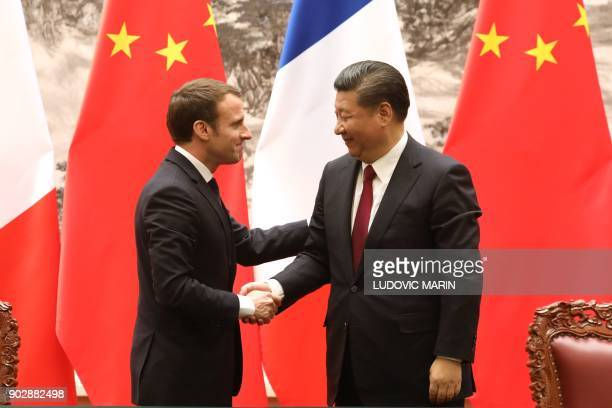 French President Emmanuel Macron and Chinese President Xi Jinping shake hands during a press conference in Beijing on January 9 2018 Chinese...