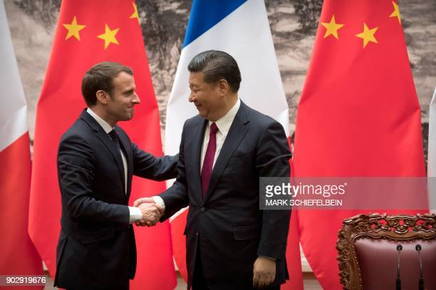 TOPSHOT French President Emmanuel Macron and Chinese President Xi Jinping shake hands after a joint press briefing at the Great Hall of the People in...