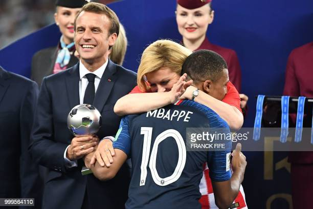 TOPSHOT French President Emmanuel Macron and Croatian President Kolinda GrabarKitarovic congratulate France's forward Kylian Mbappe during the trophy...