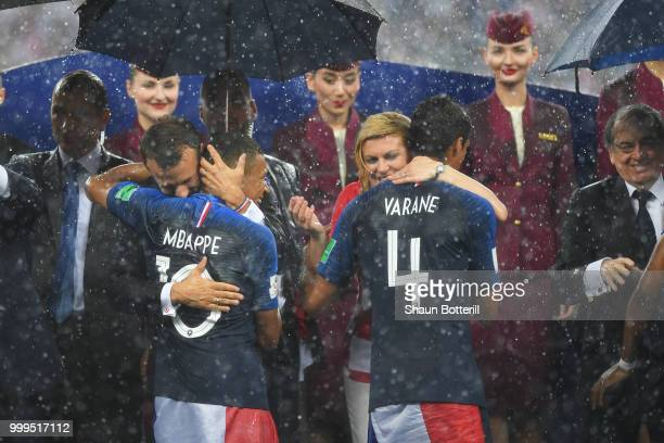 French President Emmanuel Macron and Croatia's President Kolinda GrabarKitarovic hug Kylian Mbappe anf Raphael Varane of France during the 2018 FIFA...