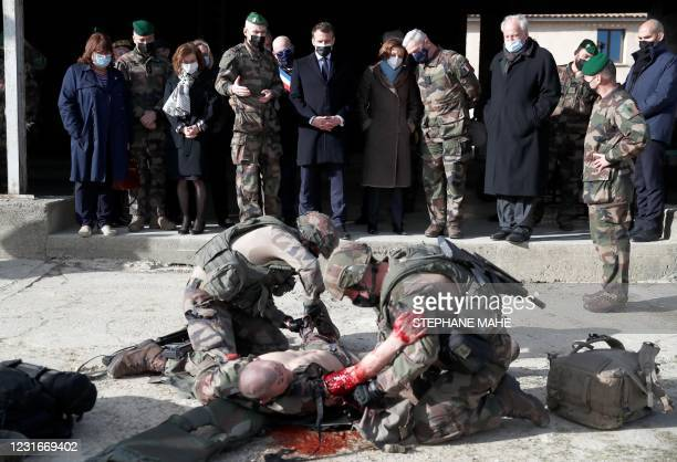 French President Emmanuel Macron and Defence Minister Florence Parly watch as soldiers carry out a rescue situation demonstration during a visit at...
