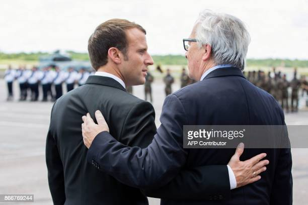 French President Emmanuel Macron and European Commission President JeanClaude Juncker embrace upon their arrival at the Cayenne FelixEboue airport at...