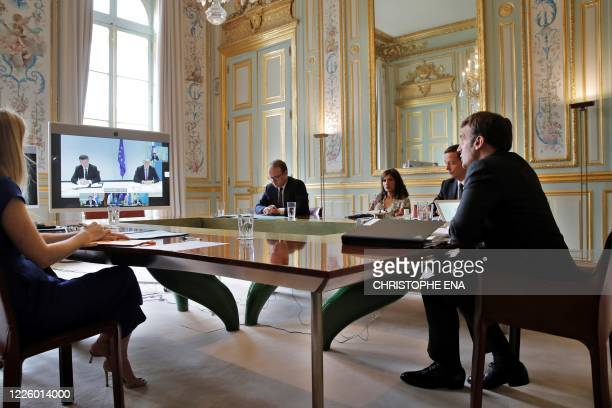 French President Emmanuel Macron , and flanked by his delegation, speaks during a visio conference with Kosovo Prime Minister Avdullah Hoti, Serbian...
