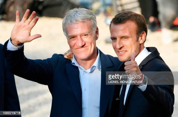 French President Emmanuel Macron and his wife Brigitte Macron pose with Didier Deschamps Hugo Lloris holding the World Cup trophy and teammates at a...