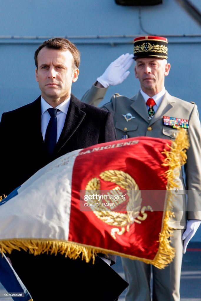 French President Emmanuel Macron (L) and French Army Chief of Staff, General Francois Lecointre stand at attention as they review French Navy personel aboard the French Mistral Class assault ship and helicopter carrier 'Dixmude', prior to attending a ceremony to present the president's wishes to the armed forces at the Toulon Naval Base in Toulon, southern France, on January 19, 2018.