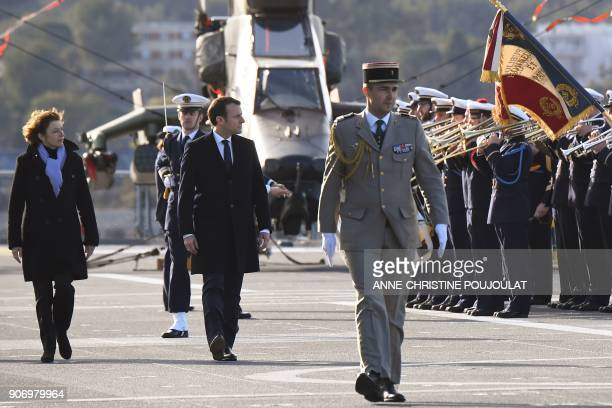French President Emmanuel Macron and French Defence Minister Florence Parly review French Navy personel as they arrive aboard the French Mistral...