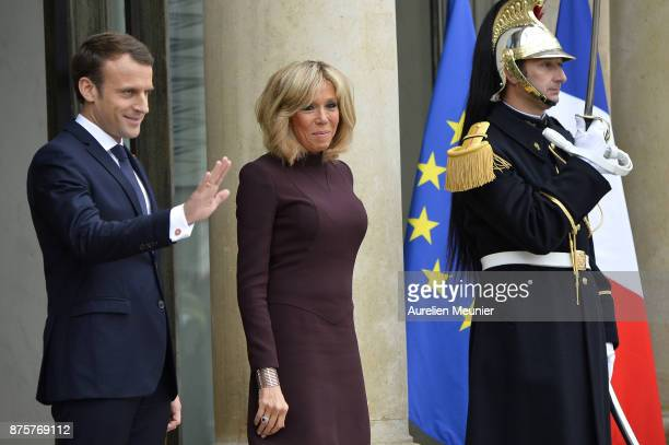 French President Emmanuel Macron and French First Lady Brigitte Macron salutes Lebanese Prime Minister Saad Hariri as he leaves the Elysee Palace on...