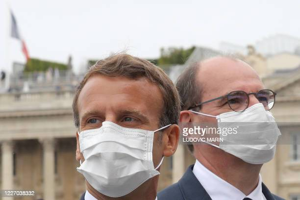 TOPSHOT French President Emmanuel Macron and French Prime Minister Jean Castex both wearing a protective facemask react at the end of the annual...
