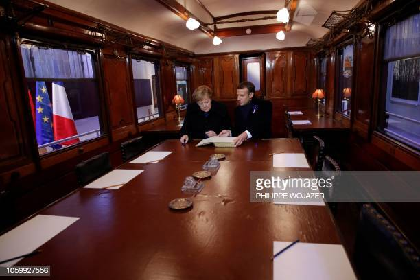 French President Emmanuel Macron and German Chancellor Angela Merkel sign on November 10, 2018 the Golden Book inside the train carriage where the...