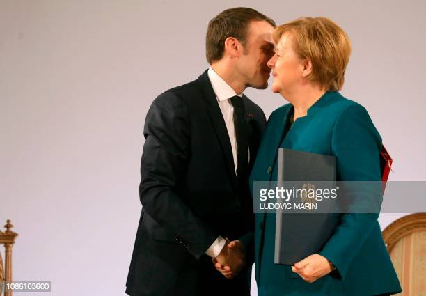 TOPSHOT French President Emmanuel Macron and German Chancellor Angela Merkel shake hands after signing a FrenchGerman friendship treaty on January 22...