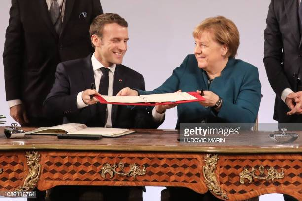 TOPSHOT French President Emmanuel Macron and German Chancellor Angela Merkel exchange the FrenchGerman friendship treaty during the signing ceremony...