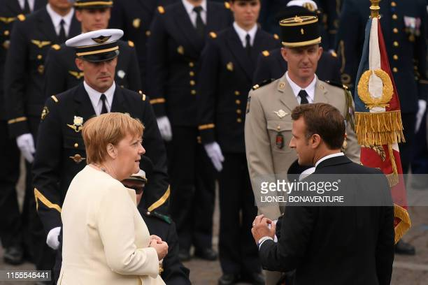 French President Emmanuel Macron and German chancellor Angela Merkel speak in front of French soldiers at the end of the Bastille Day military parade...