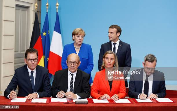 French President Emmanuel Macron and German Chancellor Angela Merkel stand as German Development Minister Gerd Mueller French Minister of Europe and...