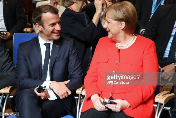 French President Emmanuel Macron and German Chancellor Angela Merkel take their seats prior to the opening of the Frankfurt Book Fair on October 10...