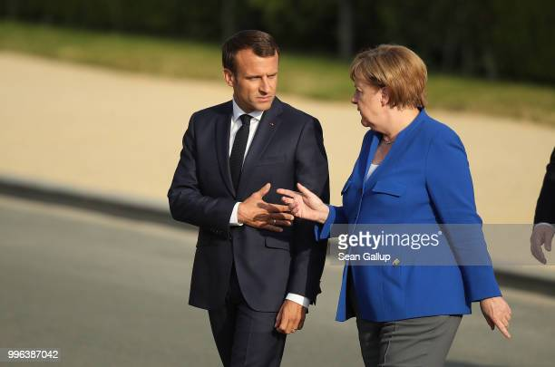 French President Emmanuel Macron and German Chancellor Angela Merkel arrive for a group photo of heads of states and governments during the evening...
