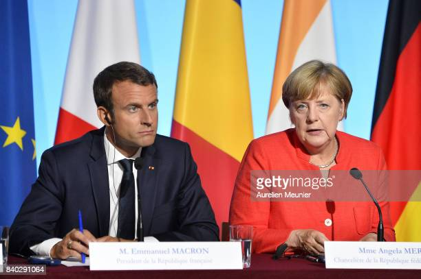 French President Emmanuel Macron and German Chancelor Angela Merkel react during a press conference after the multinational meeting at Elysee Palace...