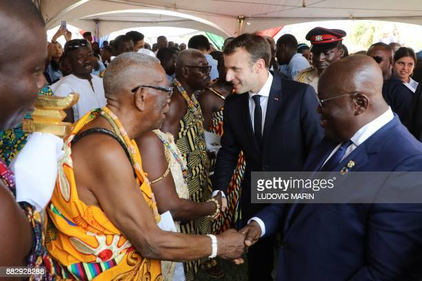 French President Emmanuel Macron and Ghana's President Nana Akufo Addo greet traditional authorities as they take part in a ceremony at the...