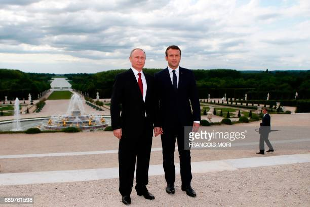 French President Emmanuel Macron and his Russian counterpart Vladimir Putin pose in the garden of the Palace of Versailles following their meeting in...