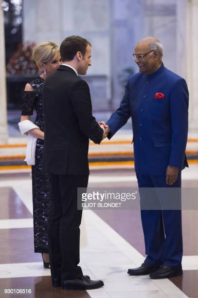 French President Emmanuel Macron and his wife Brigitte are greeted by Indian President Ram Nath Kovind as they arrive for a dinner at the...