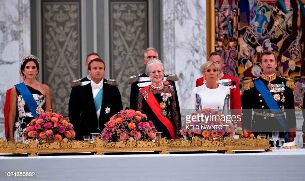 French President Emmanuel Macron and his wife Brigitte Danish Queen Margrethe Crown Princess Mary and Crown Prince Frederik stand during the State...