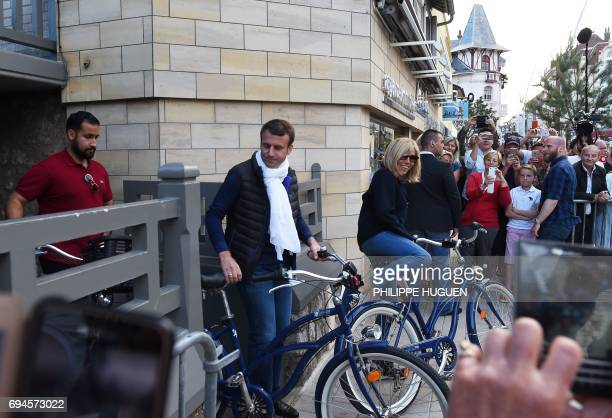 French President Emmanuel Macron and his wife Brigitte followed by Elysee senior security officer Alexandre Benalla take a bicycle ride on June 10 in...