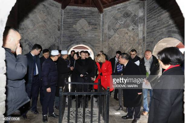 French President Emmanuel Macron and his wife Brigitte Macron are given a tour during a visit to the Great Mosque of Xian in the northern Chinese...