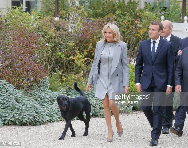 French President Emmanuel Macron and his wife Brigitte Macron arrive with their dog called Nemo to pose for a family picture with French chefs during...