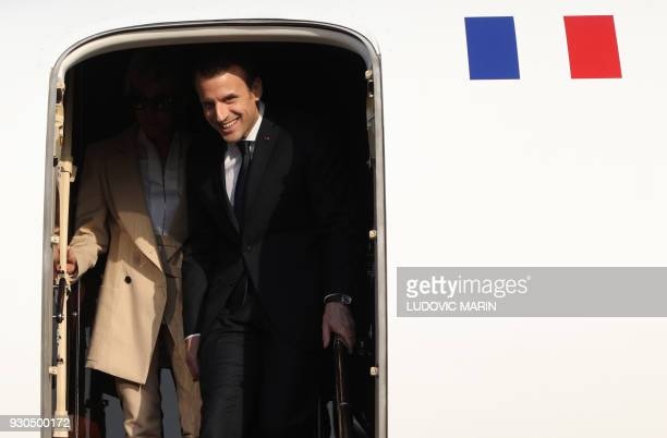 French President Emmanuel Macron and his wife Brigitte Macron go down their plane after landing at Agra aiport prior to visit to the Taj Mahal...