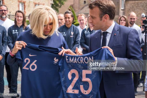 French President Emmanuel Macron and his wife Brigitte Macron hold t-shirts with their names as they meet France's national women's football team at...