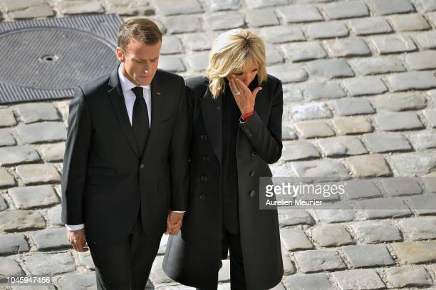 French President Emmanuel Macron and his wife Brigitte Macron leave Les Invalides after a national tribute to Charles Aznavour on October 5 2018 in...