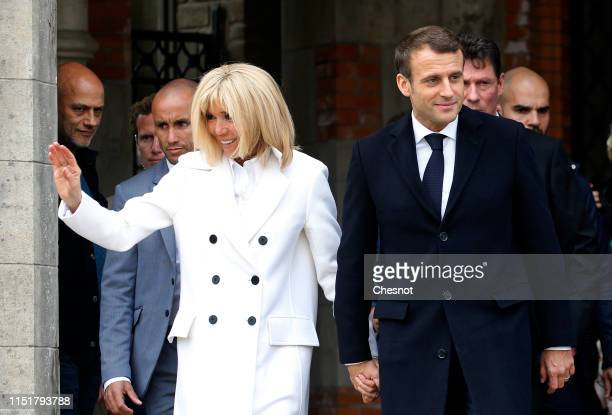 French President Emmanuel Macron and his wife Brigitte Macron leave the polling station after casting their vote in the European elections on May 26,...
