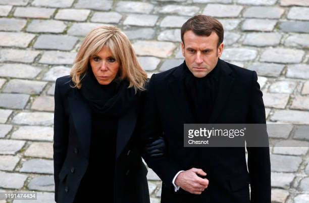 French President Emmanuel Macron and his wife Brigitte Macron leave after a national tribute ceremony to French soldiers killed in Mali at the 'Hotel...