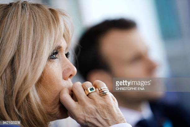 French President Emmanuel Macron and his wife Brigitte Macron listen during a meeting with hospital staff as part of a visit to the Rouen hospital...