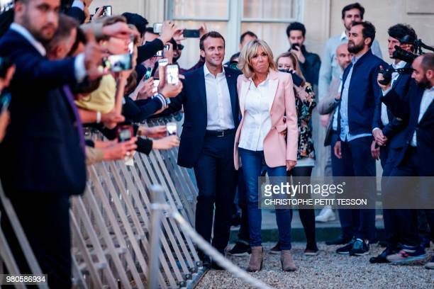 French president Emmanuel Macron and his wife Brigitte Macron listen to music next to people during the annual 'Fete de la Musique' in the courtyard...