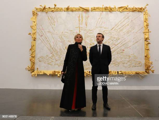 TOPSHOT French President Emmanuel Macron and his wife Brigitte Macron look at artwork during a visit to the Ullens Chinese Contemporary Art Centre in...
